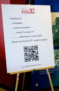 Sign at R.I.S.E. Global Forum with QR code, mobile website URL.